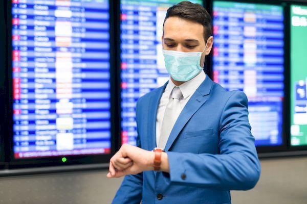 Можно ли сейчас попасть в Евросоюз? _Masked businessman checking time in the airport