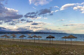 Абхазия в июне 2021 _Straw beach umbrellas on the Empty Black Sea coast in Abkhazia, Pitsunda at sunset. Pebble beach, mountains, sea, sky with clouds